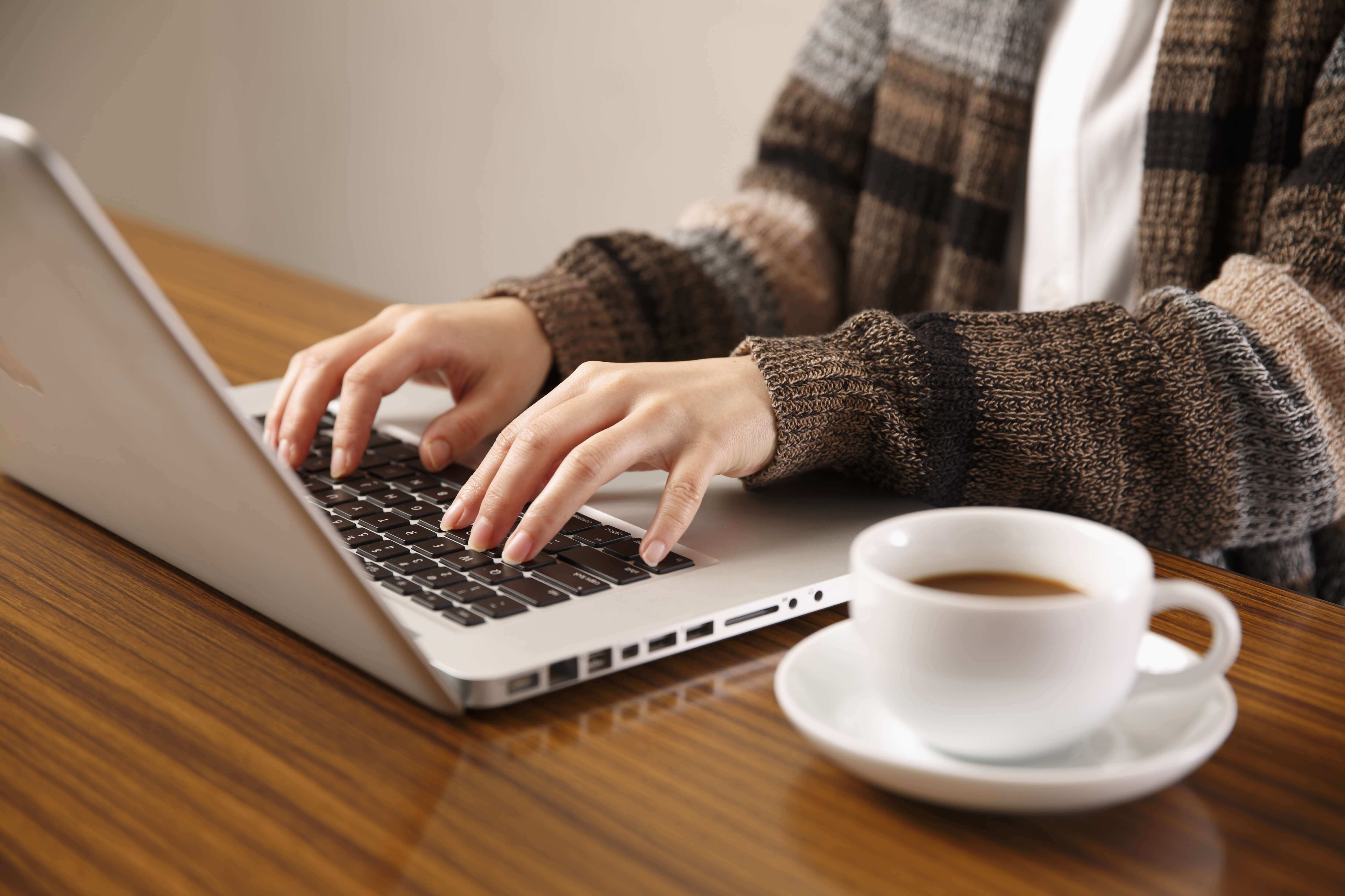 Freelancer writing proposal on the laptop at home